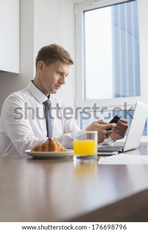 Mid adult businessman using cell phone with laptop on breakfast table - stock photo