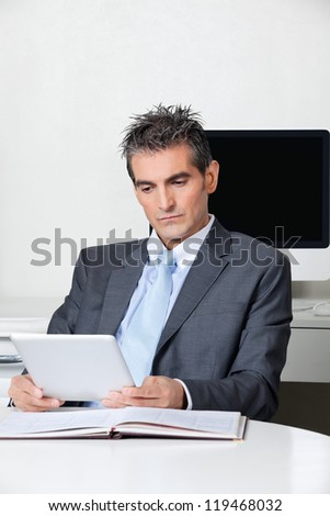 Mid adult businessman using digital tablet at desk in office - stock photo