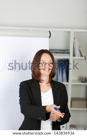 Mid adult businesswoman pointing on colleagues in office - stock photo