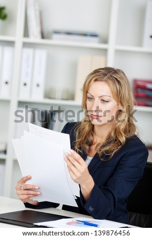 Mid adult businesswoman reading documents at office desk - stock photo