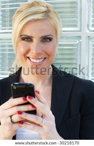 mid adult businesswoman reading phone message on smartphone and looking at camera - stock photo