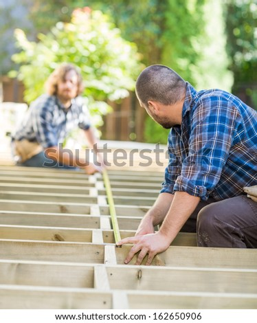 Mid adult carpenters measuring wood with tape at construction site - stock photo