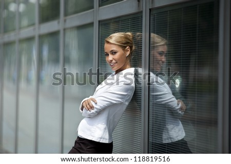 mid adult caucasian business woman looking at camera and leaning on window of office building. Side view, waist up