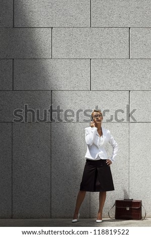 mid adult caucasian business woman talking on mobile phone and waiting near office building wall. Copy space - stock photo