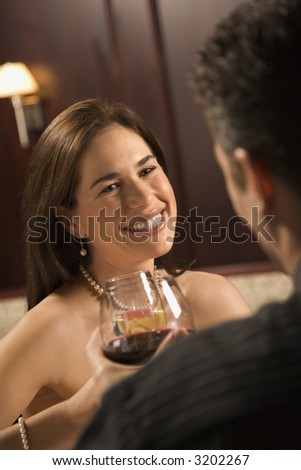 Mid adult Caucasian couple holding wine glasses and smiling. - stock photo