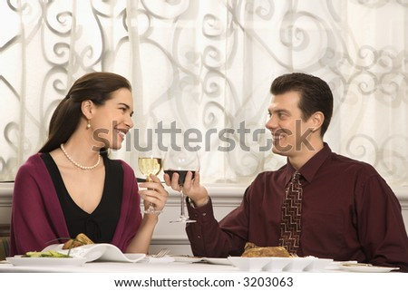 Mid adult Caucasian couple smiling and toasting wine glasses in restaurant. - stock photo