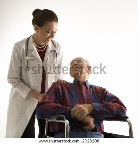 Mid-adult Caucasian female doctor looking at an elderly Caucasian male in wheelchair. - stock photo