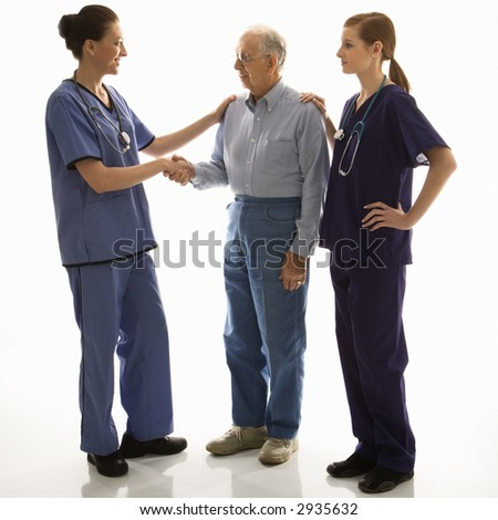 Mid-adult Caucasian female in scrubs shaking hand of elderly Caucasian male with another mid-adult Caucasian female with hand on his shoulder. - stock photo