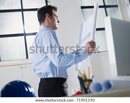 mid adult caucasian male architect examining building plan. Horizontal shape, waist up, side view - stock photo