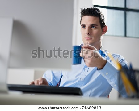 mid adult caucasian male business man looking at computer screen and holding blue coffee cup. Horizontal shape, waist up, front view - stock photo