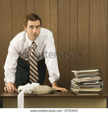 Mid-adult Caucasian male with hands on desk.
