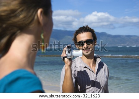 Mid-adult Caucasian man on beach pointing video camera at woman. - stock photo