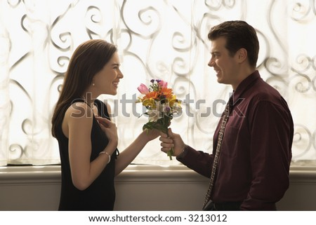 Mid adult Caucasian man presenting surprised woman with bouquet of flowers. - stock photo