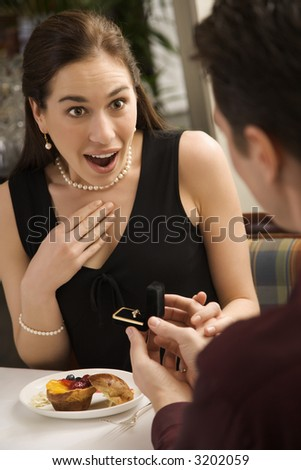 Mid adult Caucasian man proposing marriage to surprised woman at a restaurant. - stock photo