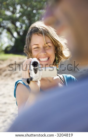 Mid-adult Caucasian woman outdoors pointing video camera at man. - stock photo