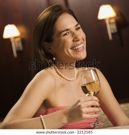 Mid adult Caucasian woman sitting at bar drinking glass of white wine and smiling. - stock photo