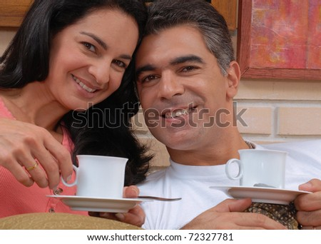 Mid adult couple drinking coffee in a living room. - stock photo