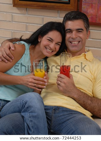 Mid adult couple drinking fruit juice in a living room. Couple drinking and sharing in a living room. - stock photo