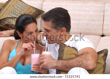 Mid adult couple drinking strawberry milkshake in a living room. - stock photo