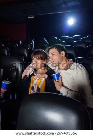 Mid adult couple having snacks while watching movie in cinema theater - stock photo