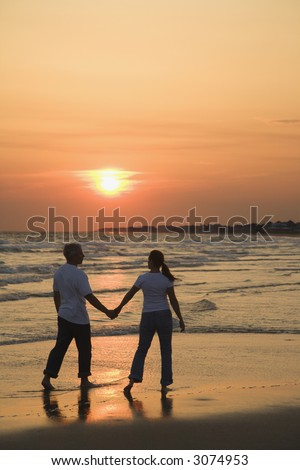 Mid-adult couple holding hands and walking on beach at sunset.