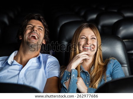 Mid adult couple laughing while watching film in movie theater - stock photo