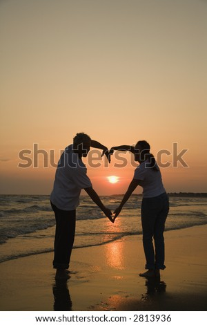 Mid-adult couple making heart shape with arms on beach at sunset. - stock photo