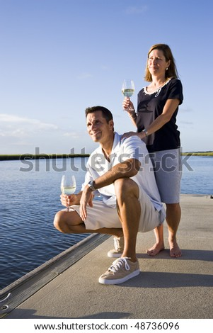 Mid-adult couple on dock by water enjoying drink on sunny day - stock photo