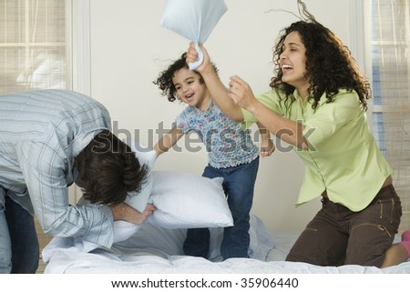 Mid adult couple playing with their daughter - stock photo