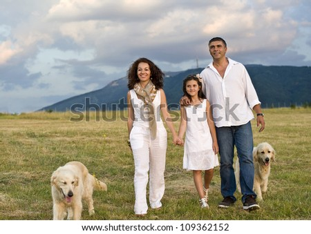 Mid adult couple with daughter and dogs in the park - stock photo