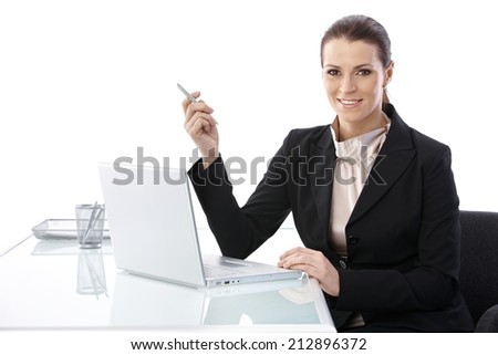 Mid-adult elegant businesswoman sitting at desk, using laptop computer holding pen, smiling at camera. - stock photo