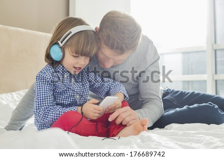 Mid adult father with boy listening music on headphones in bedroom - stock photo
