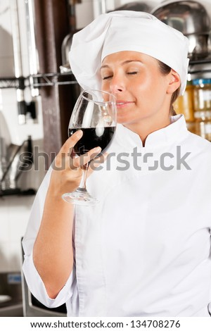 Mid adult female chef smelling red wine in commercial kitchen - stock photo