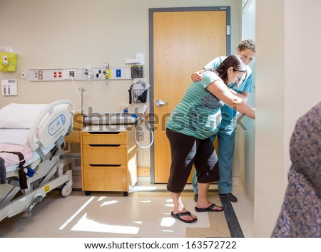Mid adult female nurse comforting tensed pregnant woman leaning on window sill in hospital room - stock photo