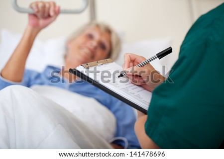 Mid adult female nurse writing on clipboard while looking at patient in hospital - stock photo