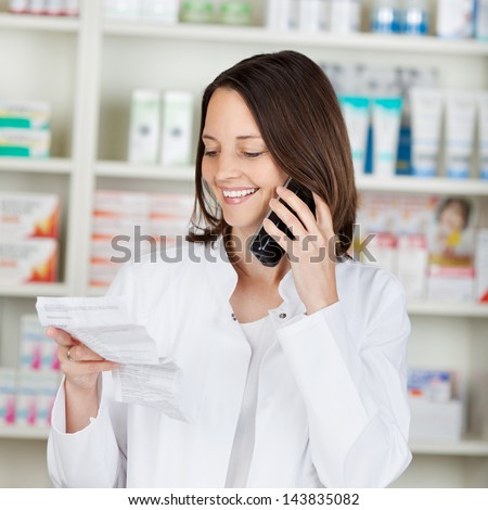 Mid adult female pharmacist holding prescription paper while using cordless phone in pharmacy - stock photo