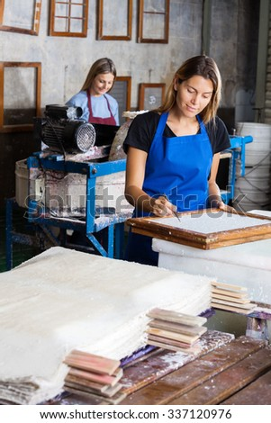 Mid adult female worker using tweezers to clean paper on mold in factory - stock photo