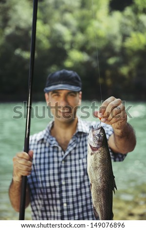 mid adult fisherman on holidays on river, relaxing and fishing trout. Focus on fish - stock photo
