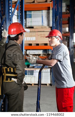 Mid adult foreman communicating with young coworker at warehouse - stock photo