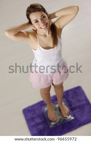 Mid adult happy caucasian woman on scales at home expressing satisfaction and joy for losing weight. High angle view - stock photo