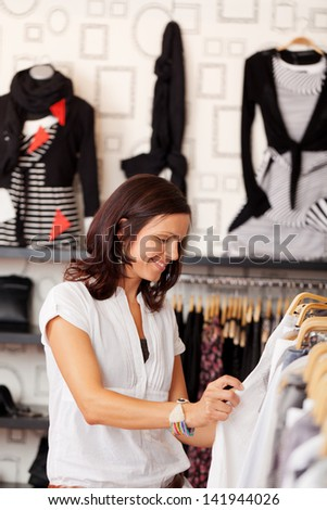 Mid adult happy female customer looking at clothes in clothing store