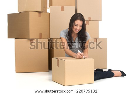 mid adult happy woman during move with boxes at new flat. young woman writing on boxes and smiling while moving to new apartment - stock photo
