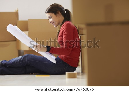 mid adult happy woman moving with boxes at new home and looking at blueprint. Side view, Copy space - stock photo