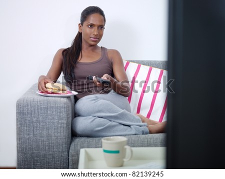 mid adult indian woman on sofa, changing tv channel with remote control and eating junk food. Front view, copy space