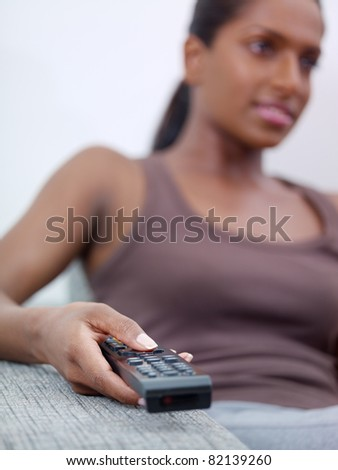 mid adult indian woman on sofa, changing tv channel with remote control. Front view, copy space