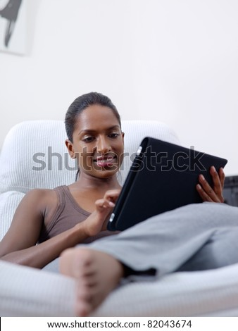 mid adult indian woman relaxing on armchair and using touch pad computer. Vertical shape, front view, copy space