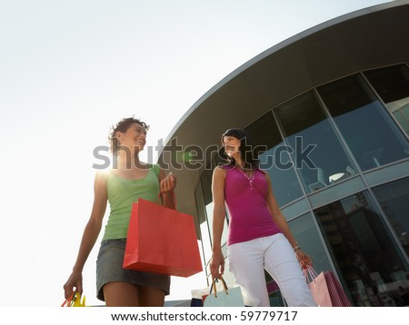 mid adult italian woman and hispanic woman carrying shopping bags out of shopping center at sunset. Horizontal shape, low angle view, copy space - stock photo