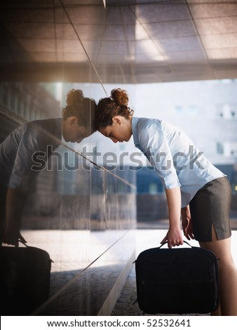mid adult italian woman banging her head against a wall outside office building. Vertical shape, copy space - stock photo