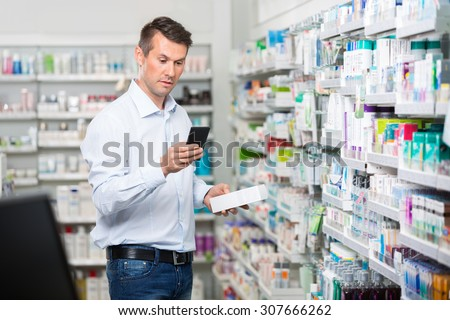 Mid adult male consumer checking information on mobile phone while holding product in pharmacy - stock photo