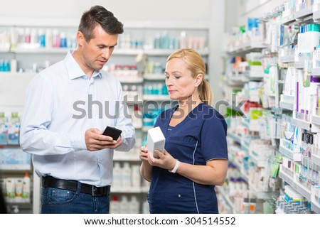 Mid adult male customer showing product information on mobile phone to pharmacist in pharmacy - stock photo